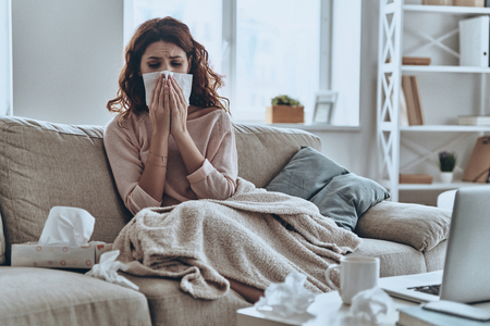 Sneezing just keep coming. Sick young women blowing her nose using facial tissues while sitting on the sofa at home