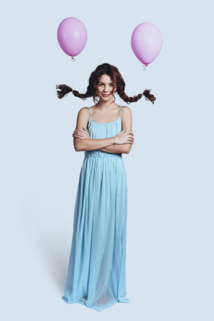 Simply stunning. Full length of beautiful young woman with balloons tied to her pigtails smiling and looking at camera and smiling while standing against grey background  Stock fotó