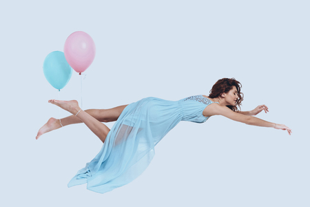 Dream fly. Studio shot of attractive young woman in elegant dress keeping arms outstretched while hovering against grey background  Stock Photo
