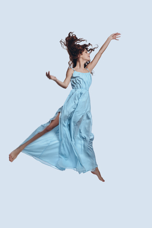 Reaching the sky. Full length studio shot of attractive young woman in elegant dress gesturing while hovering against grey background              스톡 콘텐츠