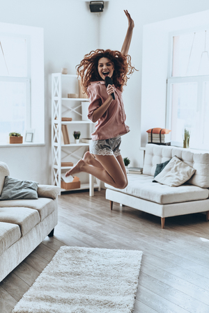 Mid-air fun. Full length of attractive young women singing using comb and smiling while jumping at home