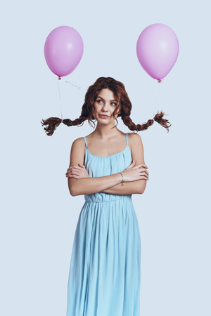 What if... Studio shot of beautiful young woman with balloons tied to her pigtails smiling and looking at camera while standing against grey background Banco de Imagens
