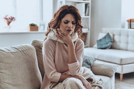 Ziek zijn. Zieke jonge vrouwen bedekt met deken hoesten terwijl ze thuis op de bank zitten