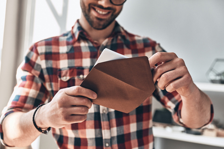 Recibiendo tarjeta de felicitación. Cerca del joven abriendo un sobre y sonriendo mientras está de pie en el interior Foto de archivo