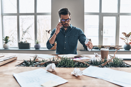Staying connected. Handsome young man talking on smart phone and crumpling paper while sitting in the office Stock Photo