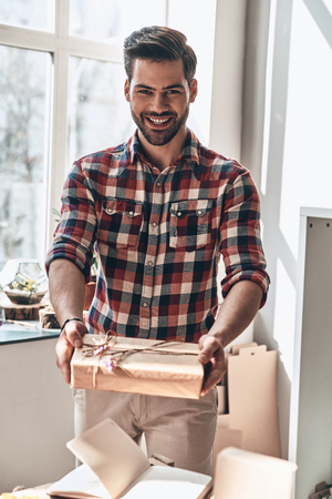 With love for you. Handsome young man giving a gift box and looking at camera with smile while standing in the creative working space Reklamní fotografie