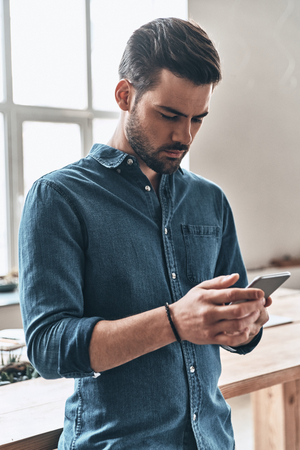 Quick message to client.  Handsome young man holding smart phone and looking at it while standing in the office Stock Photo