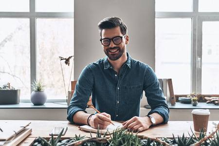 Young and successful. Handsome young man writing something down in personal organizer and smiling while sitting in the office