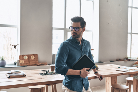 Confident and handsome. Handsome young man holding digital tablet and looking away while standing in the office                  Stock Photo