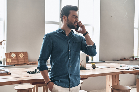 Good talk with client. Handsome young man talking on smart phone and looking away with smile while standing in the office
