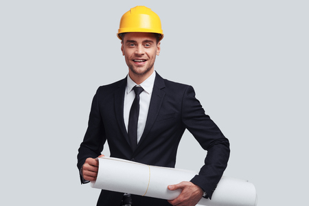 Achieving best results. Good looking young man in hardhat carrying blueprint and smiling while standing against grey background