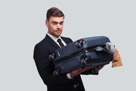 How to deal with this luggage? Good looking young man carrying full over packed suitcase while standing against grey background