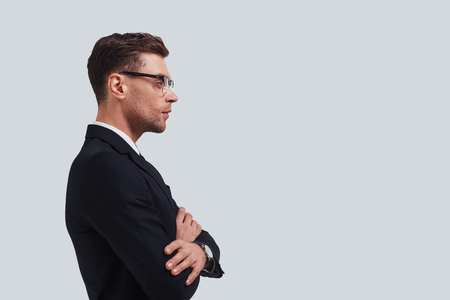 Thinking about solution. Serious young man in full suit keeping arms crossed and looking away while standing against grey background