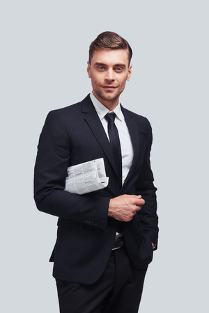 Confident business expert. Good looking young man in full suit smiling and looking at camera while standing against grey background Stock Photo
