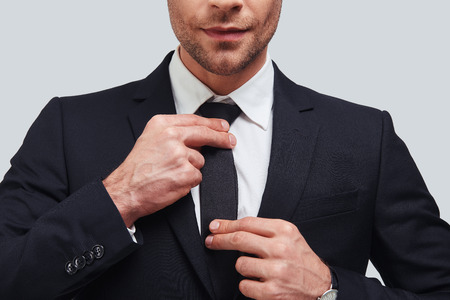 Everything must be perfect. Close up of young man in full suit adjusting his necktie while standing against grey background