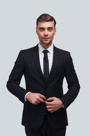 Young and successful. Handsome young man in full suit adjusting his jacket and looking at camera while standing against grey background
