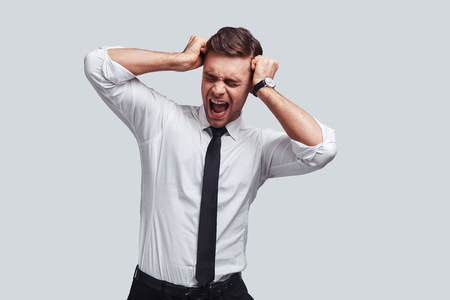 Despair. Frustrated young man in full suit touching his head with hands and screaming while standing against grey background