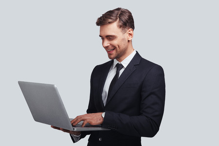 Ready to work hard. Good looking young man in full suit using laptop and smiling while standing against grey background 版權商用圖片