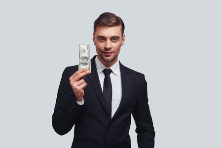 Measurement of success. Good looking young man in full suit smiling and holding a paper currency while standing against grey background Stock Photo