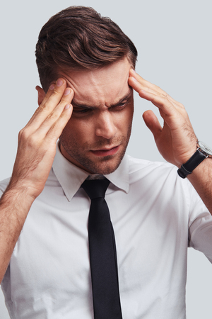Terrible headache. Frustrated young man in full suit touching his head with hands while standing against grey background