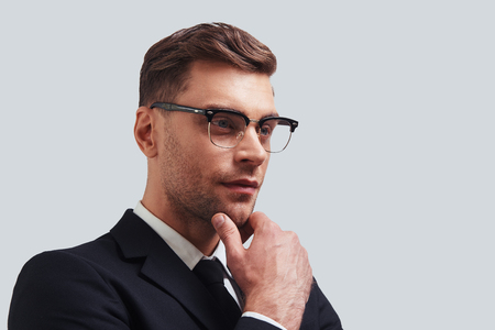 Thoughtful businessman. Serious young man in full suit keeping hand on chin and looking away while standing against grey background