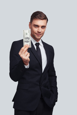 Making money. Good looking young man in full suit smiling and holding a paper currency while standing against grey background Stock Photo
