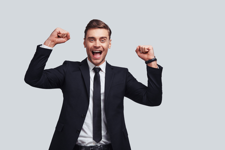 Victory! Good looking young man in full suit gesturing and smiling while standing against grey background