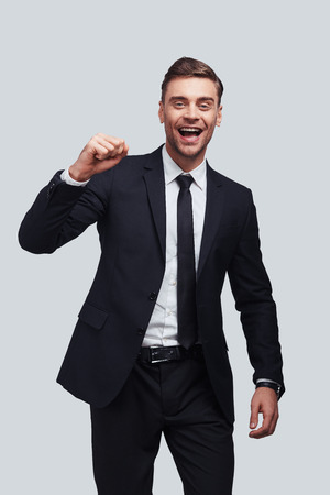 Success! Good looking young man in full suit gesturing and smiling while standing against grey background