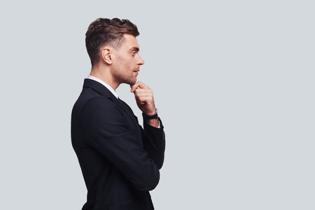 Taking time to think. Serious young man in full suit keeping hand on chin and looking away while standing against grey background