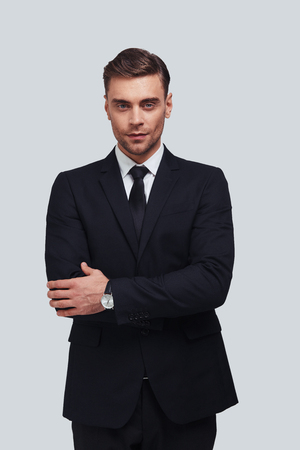 Confident in his style. Handsome young man in full suit keeping arms crossed and looking at camera while standing against grey background