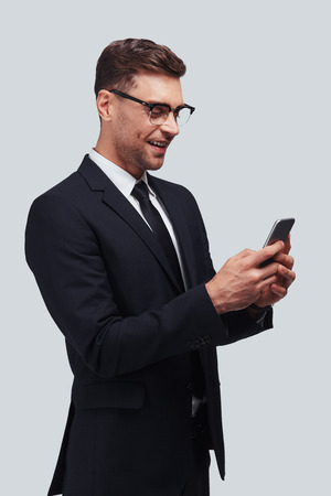 Receiving good feedbacks. Handsome young man using his smart phone and smiling while standing against grey background Stock Photo