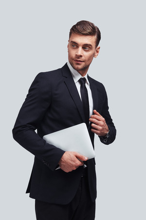 Taking care of business. Handsome young man carrying digital tablet while standing against grey background
