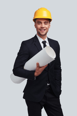Young architect. Good looking young man in hardhat carrying blueprint and smiling while standing against grey background