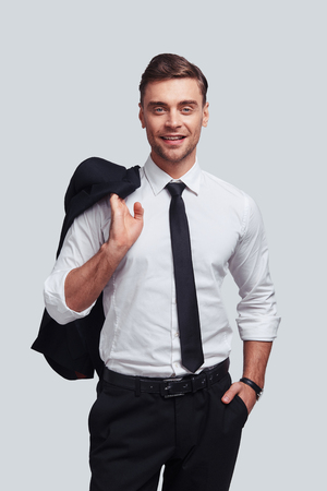 Confident and handsome. Good looking young man carrying his jacket on shoulders and smiling while standing against grey background