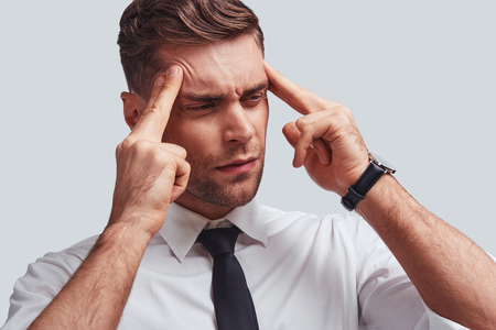 Terrible pain. Frustrated young man in full suit touching his head with hands while standing against grey background