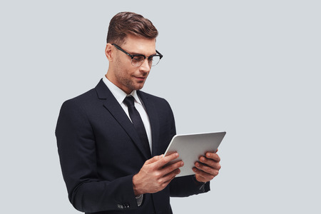 Concentrated at work. Handsome young man using digital tablet while standing against grey background