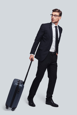 In a hurry. Full length of good looking young man with suitcase looking away while standing against grey background