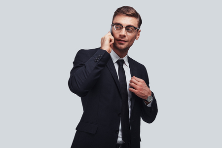 Good business talk. Handsome young man talking on smart phone and looking away with smile while standing against grey background