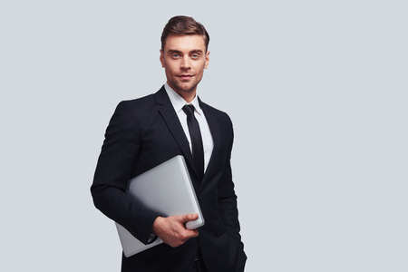 Pure confidence. Good looking young man in full suit carrying laptop and smiling while standing against grey background Stock fotó