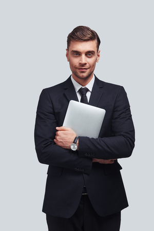 Young and successful. Handsome young man carrying digital tablet and looking at camera with smile while standing against grey background Stock fotó