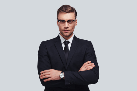 Portrait of confidence. Handsome young man in full suit keeping arms crossed and looking at camera while standing against grey background Stock Photo