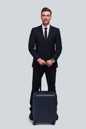 Business travel. Full length of good looking young man with suitcase smiling and looking at camera while standing against grey background