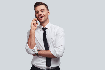 Discussing business. Handsome young man in shirt and tie talking on smart phone and looking away with smile while standing against grey background