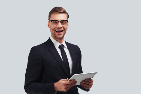 How may I help you? Handsome young man using digital tablet and smiling while standing against grey background