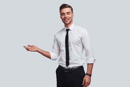 Over here! Good looking young man pointing copy space and smiling while standing against grey background