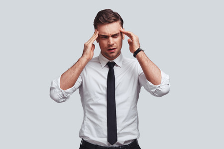 Overworked. Frustrated young man in full suit touching his head with hands while standing against grey background