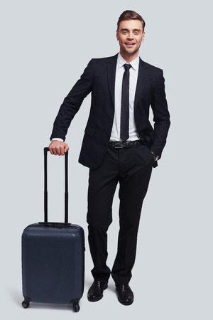 Time to travel. Full length of good looking young man with suitcase smiling and looking at camera while standing against grey background