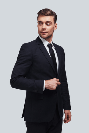 Always perfect. Handsome young man in full suit adjusting his jacket and looking away while standing against grey background