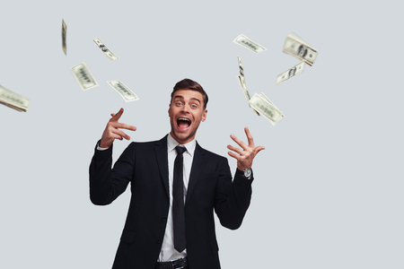 Finally rich. Good looking young man surrounded by flying money keeping mouth open while standing against grey background Stock Photo