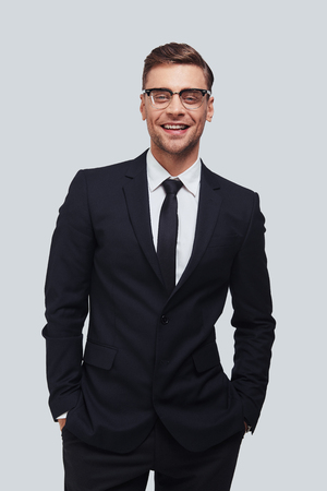 Perfect in his style. Handsome young man in full suit keeping hands in pockets and looking at camera with smile while standing against grey background